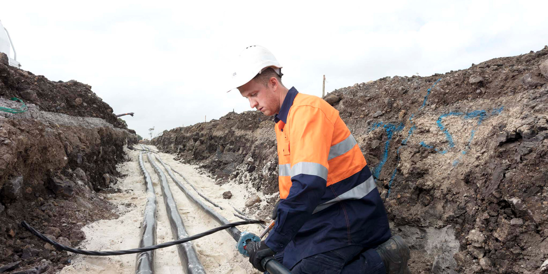 Workman in trench with electrical cables
